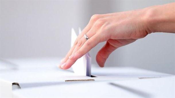 Una persona deposita su voto en la urna.