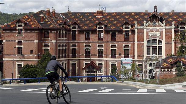 Una persona en una bicicleta frente al Hospital de Basurto.